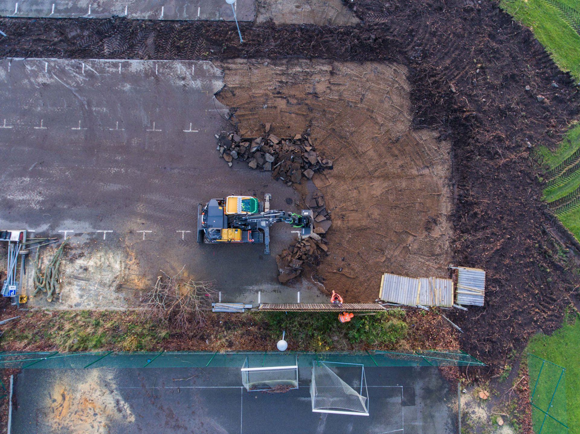Grävskopa tar bort asfalten från Vikenskolans parkering och arbetare tar ned staket. Taget uppifrån ned