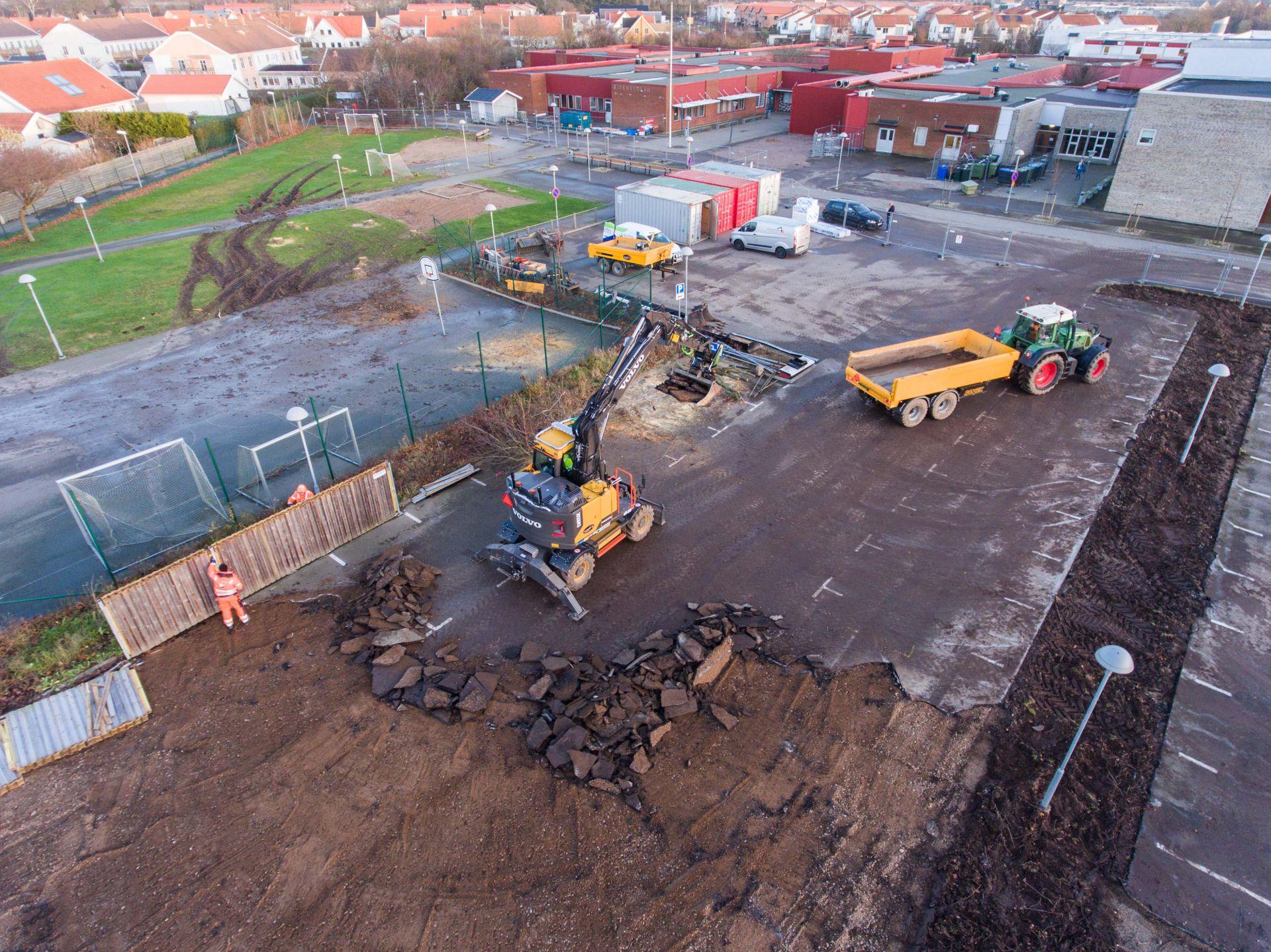 Grävskopa lastar asfalten från Vikenskolans parkering till släp och arbetare tar ned staket.