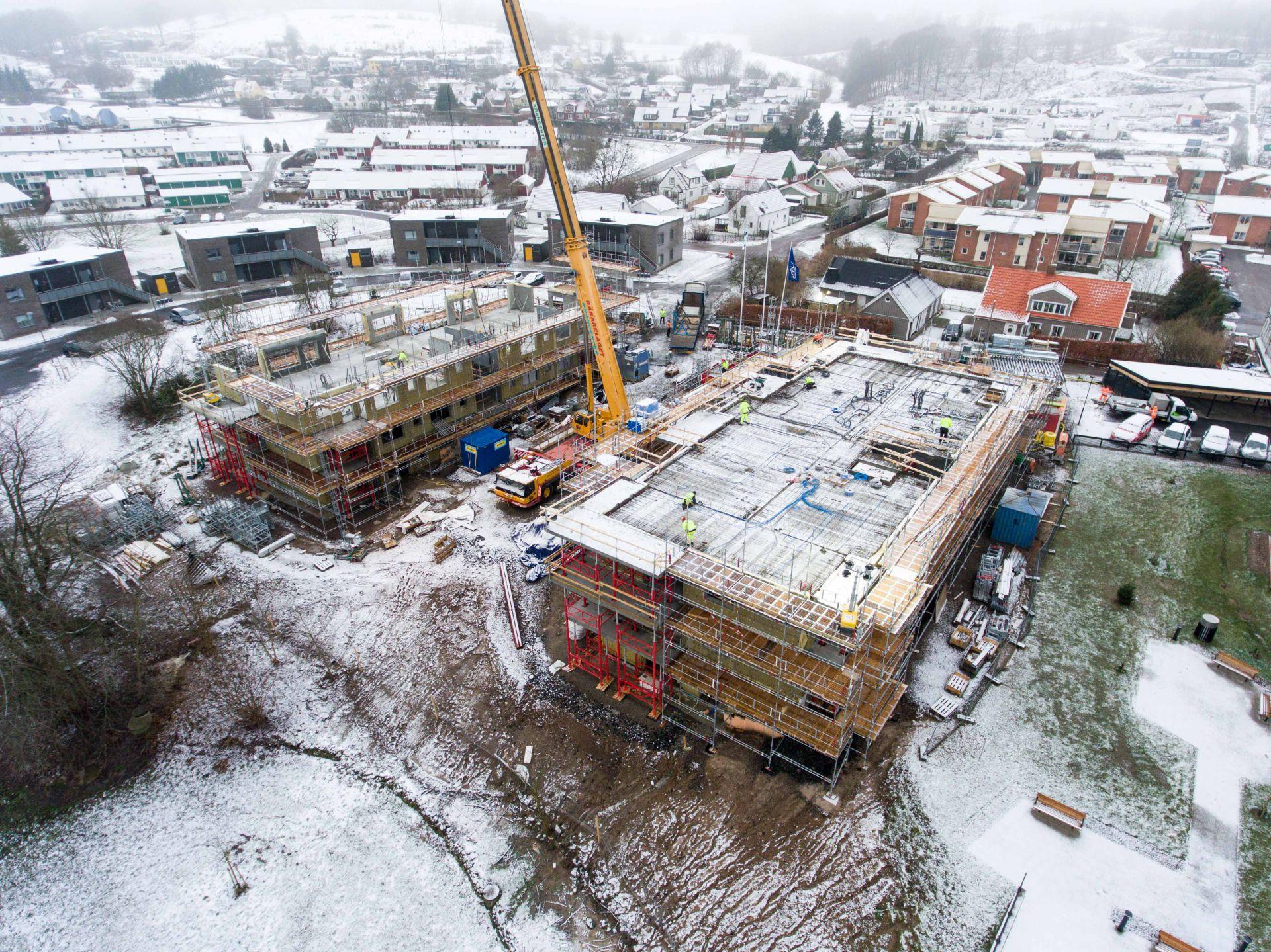 Byggplats för Apelgården och Armobacken i Båstad med överblick utav samhället i vinterlandskap