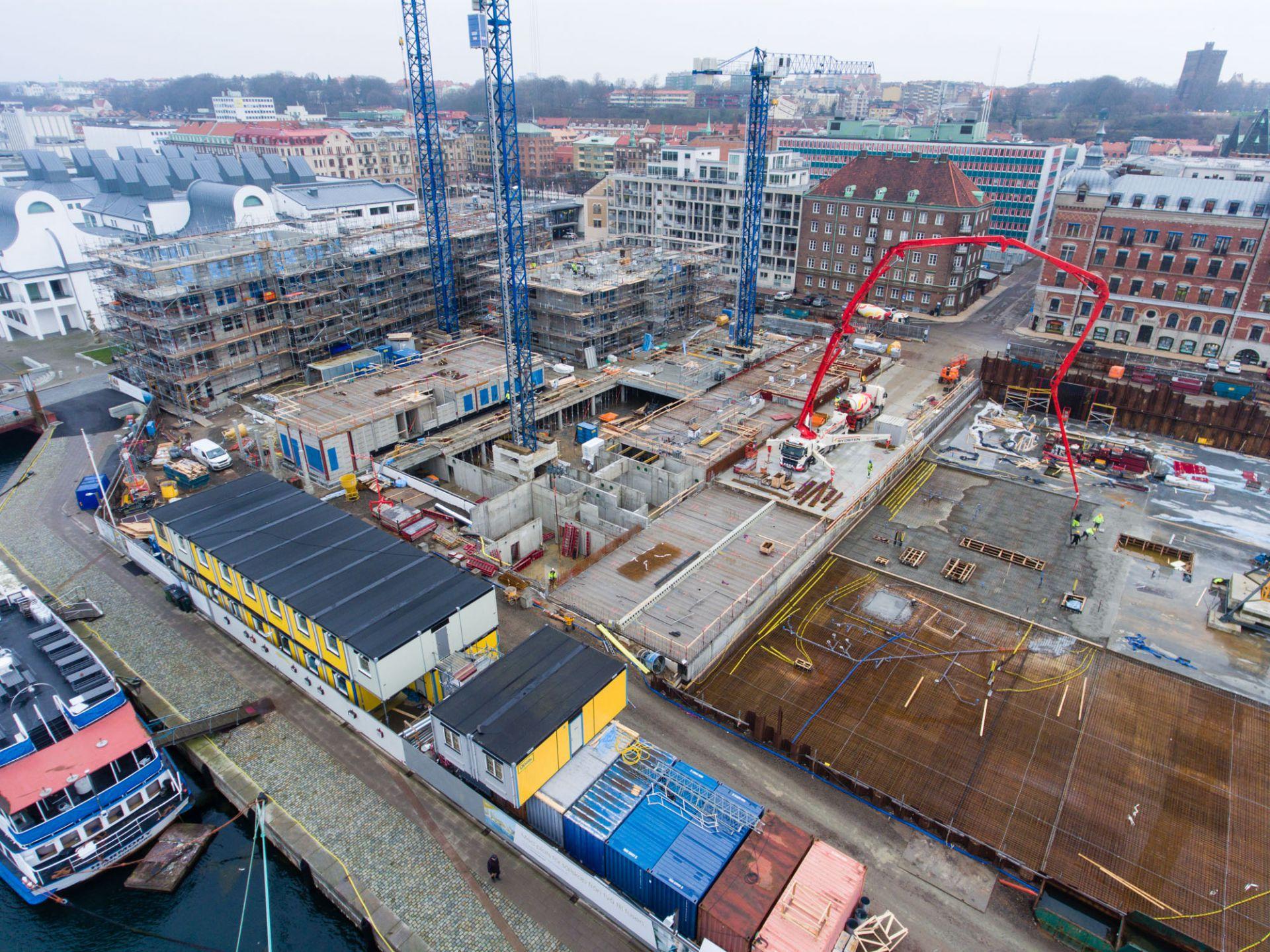 Översikt utav byggplatsen för kongresshuset mitt i Helsingborg vid kajkanten och höghusen runtomkring.