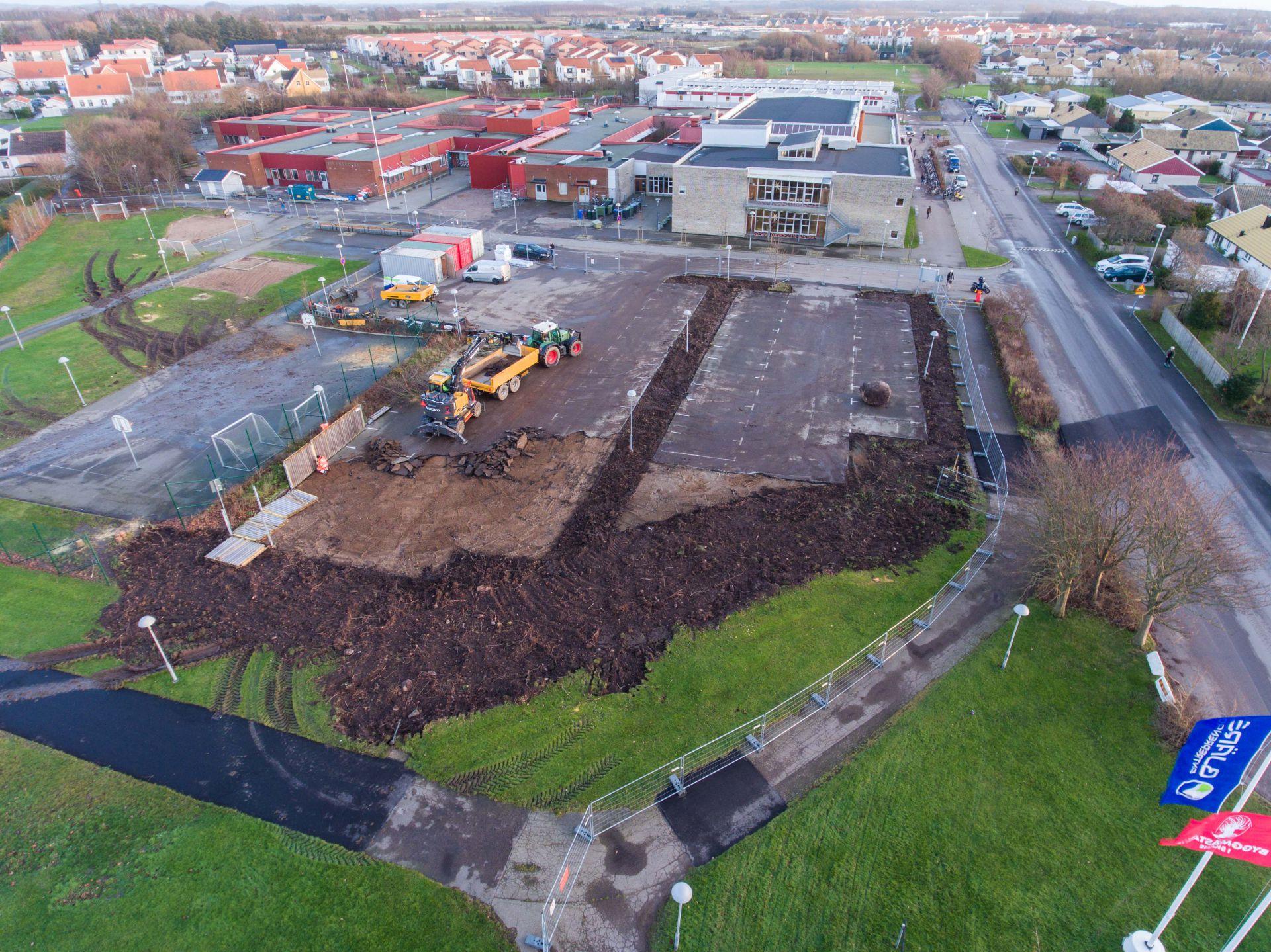 Grävskopa lastar asfalten från Vikenskolans parkering till släp och arbetare tar ned staket. Samhället i bakgrunden