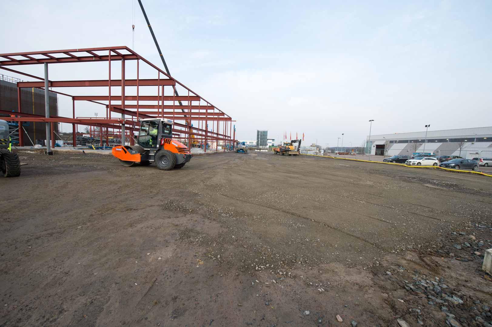 Olika maskiner gör grundläggningen av Porschecenter i Helsingborg med byggställningen i bakgrunden